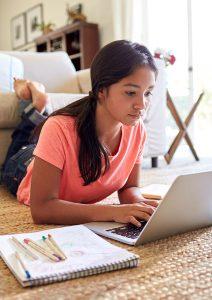 Student using laptop on floor